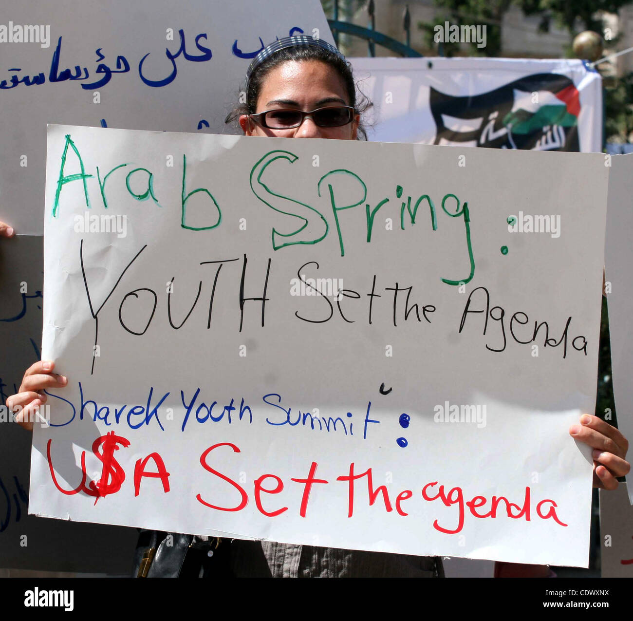 Palestinian youths hold placards bearing anti US and USAID slogans during a protest against United States policies - Stock Image