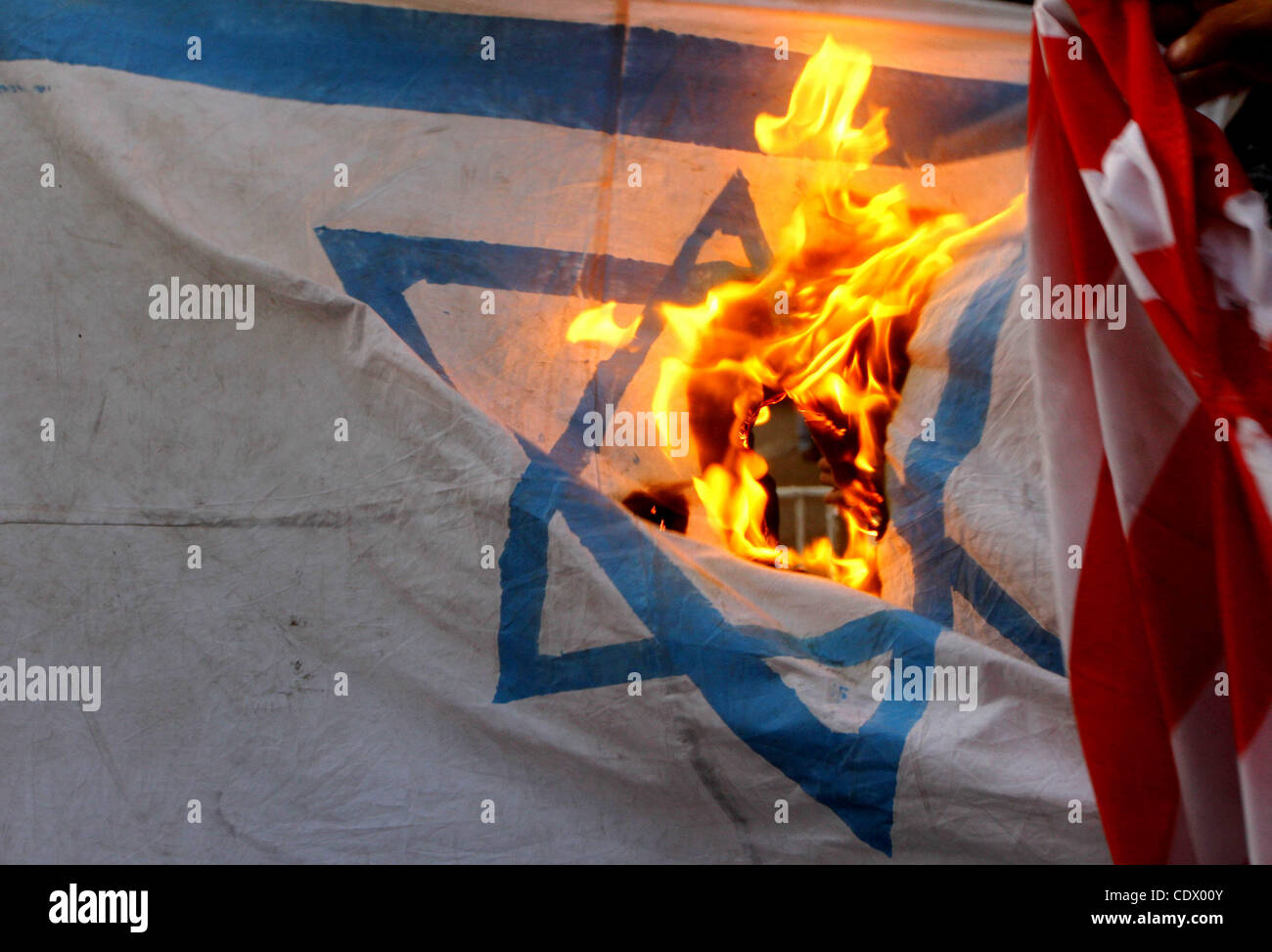 Palestinian militants of Popular Resistance Committees burn an Israeli and American flags during a rally to mark - Stock Image