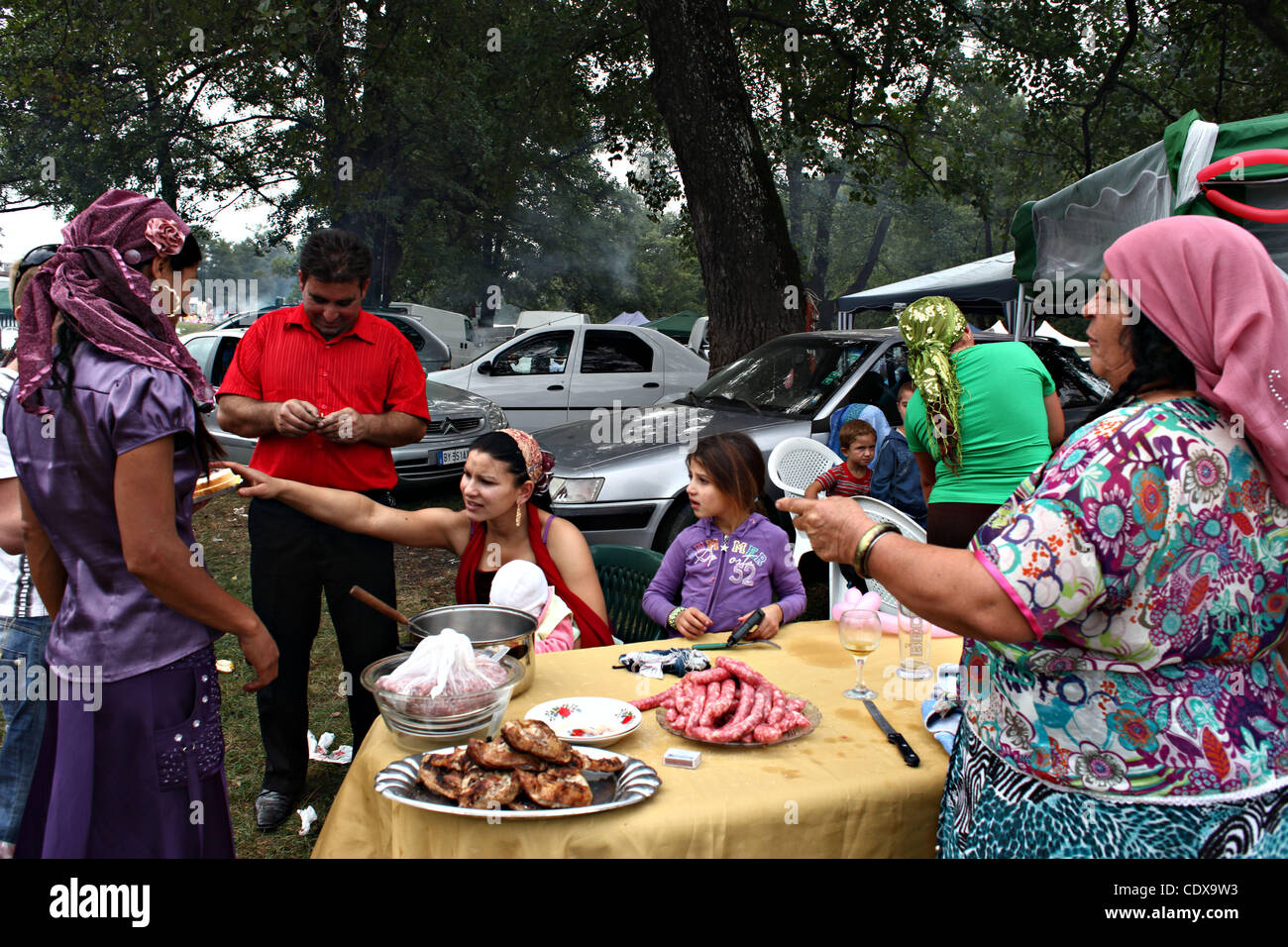 A Roma family prepares food in Costesti, Romania, during an anual religious celebation that gathers thousands of - Stock Image