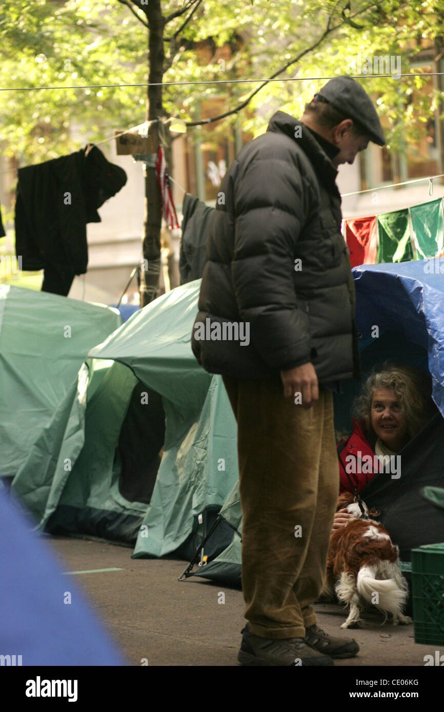 An Occupy Wall Street protester in her tent with a dog in Zuccotti Park. - Stock Image
