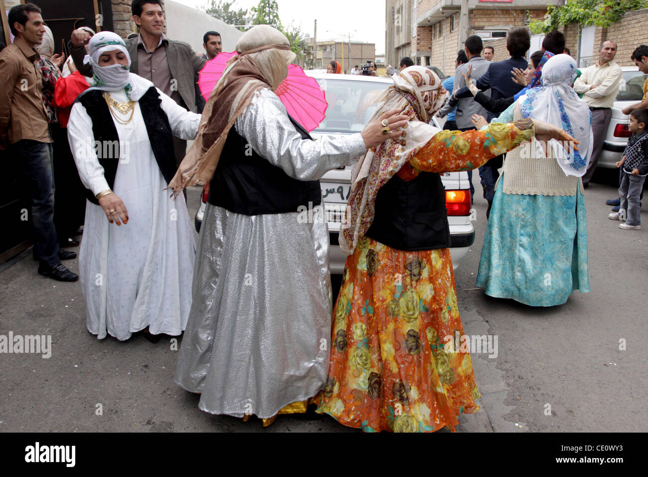 September 11, 2011: Women dance with traditional dresses around the wedding car during a wedding party in Moghan - Stock Image