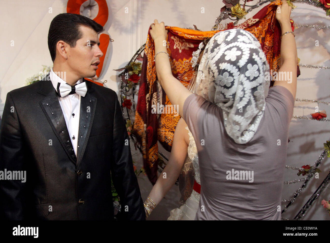 September 11, 2011: A girl (right) helps bride Khadija (right - covered) to uncover her shawl while groom Abbas - Stock Image