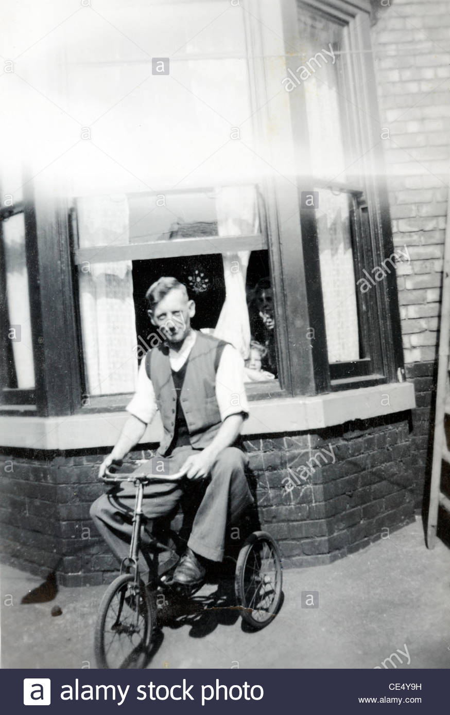 adult person on a child bicycle posing in front of house England 1940s - Stock Image