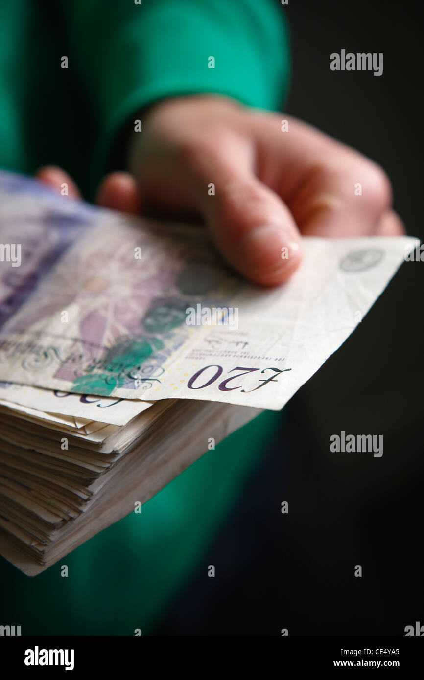 holding fan of money £20 notes GBR sterling currency hands stash wad taking note off - Stock Image