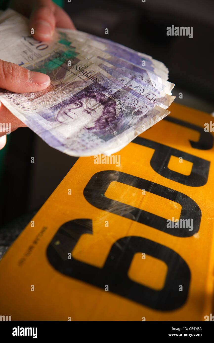 holding fan of money £20 notes GBR sterling currency number plate illegal fraud - Stock Image