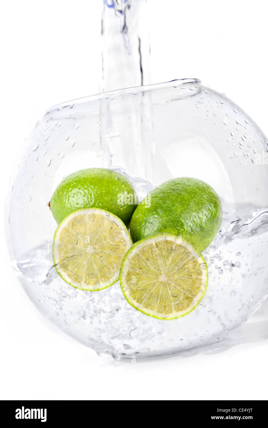 Green limes in water dropped isolated on a white - Stock Image