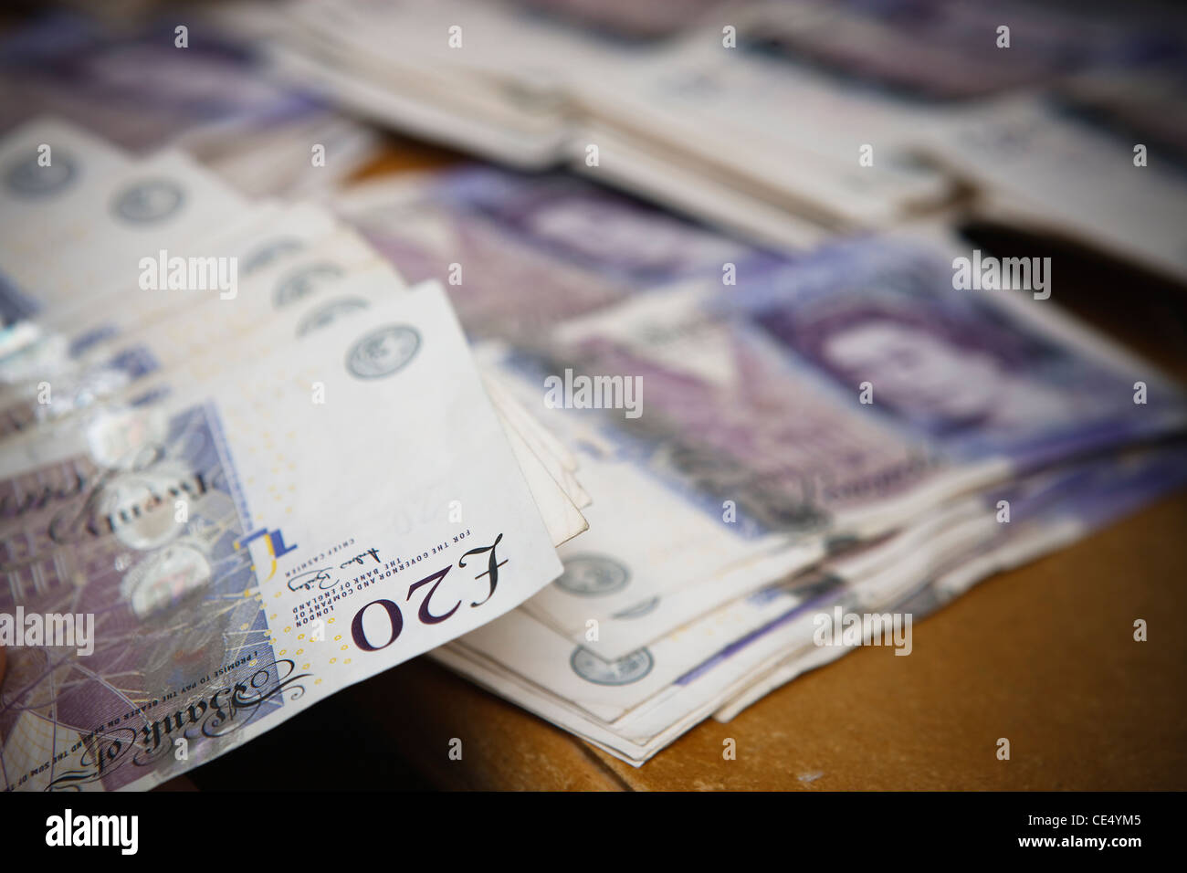Counting money fan £20 notes GBR sterling currency desk view landscape piles - Stock Image