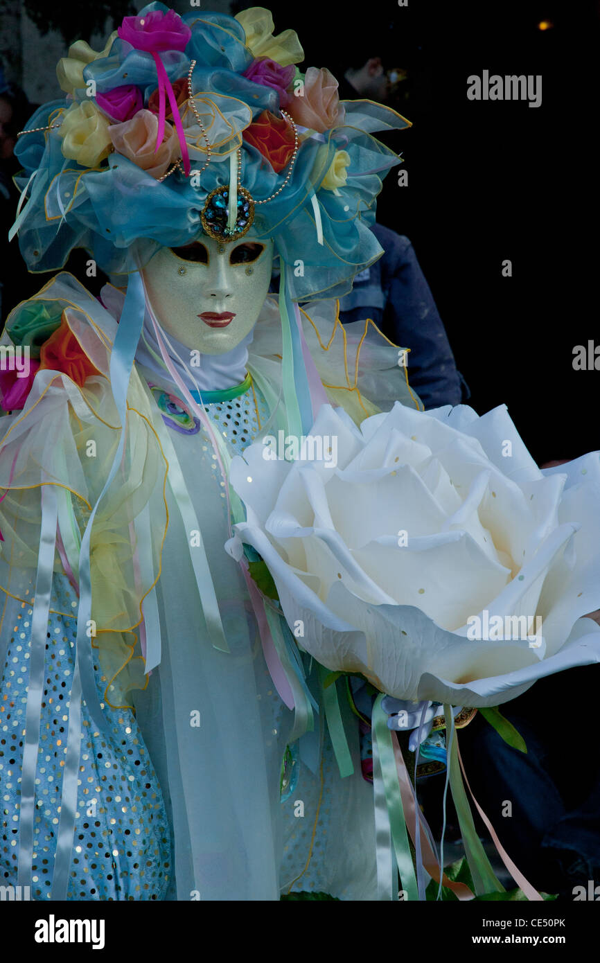 An image taken during Venice Carnival in 2010 featuring a mask wearing carnival goer with flower ornaments - Stock Image
