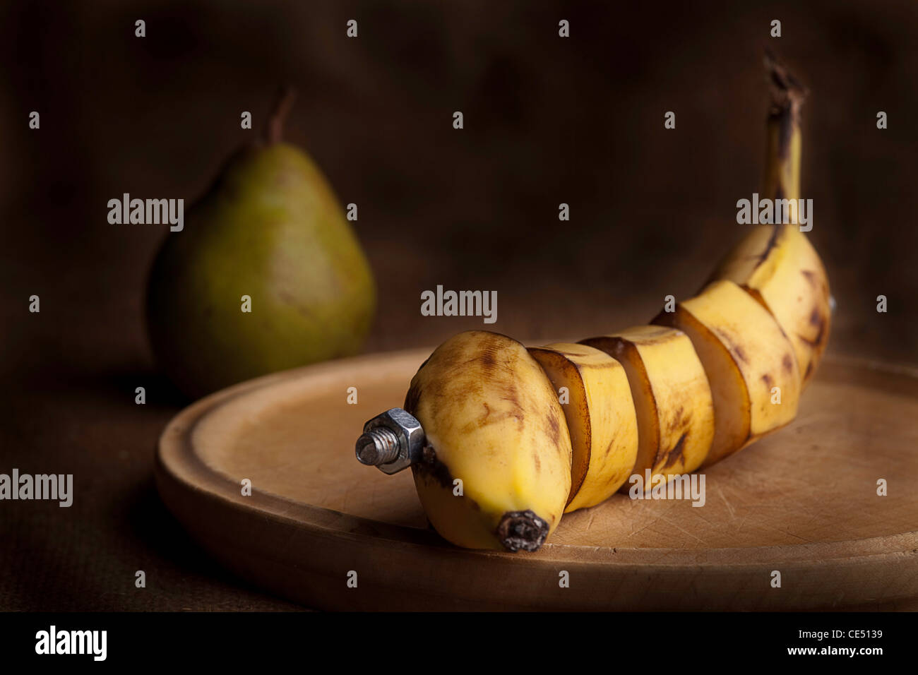 banana manipulated fruit with bolt holding it together - Stock Image