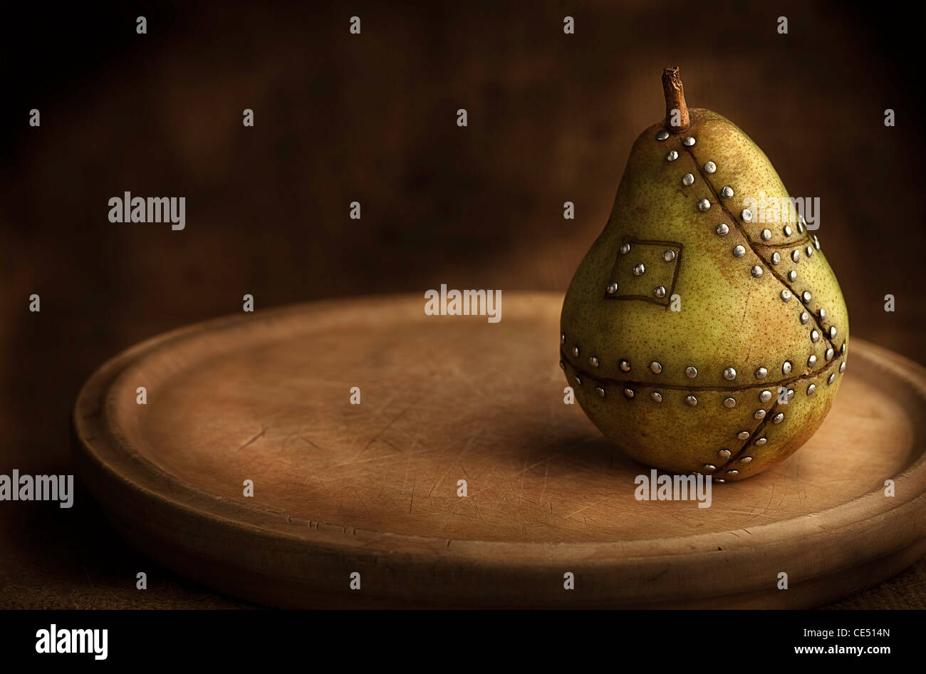 pear manipulated fruit with nails holding it together concept for genetic manipulation - Stock Image