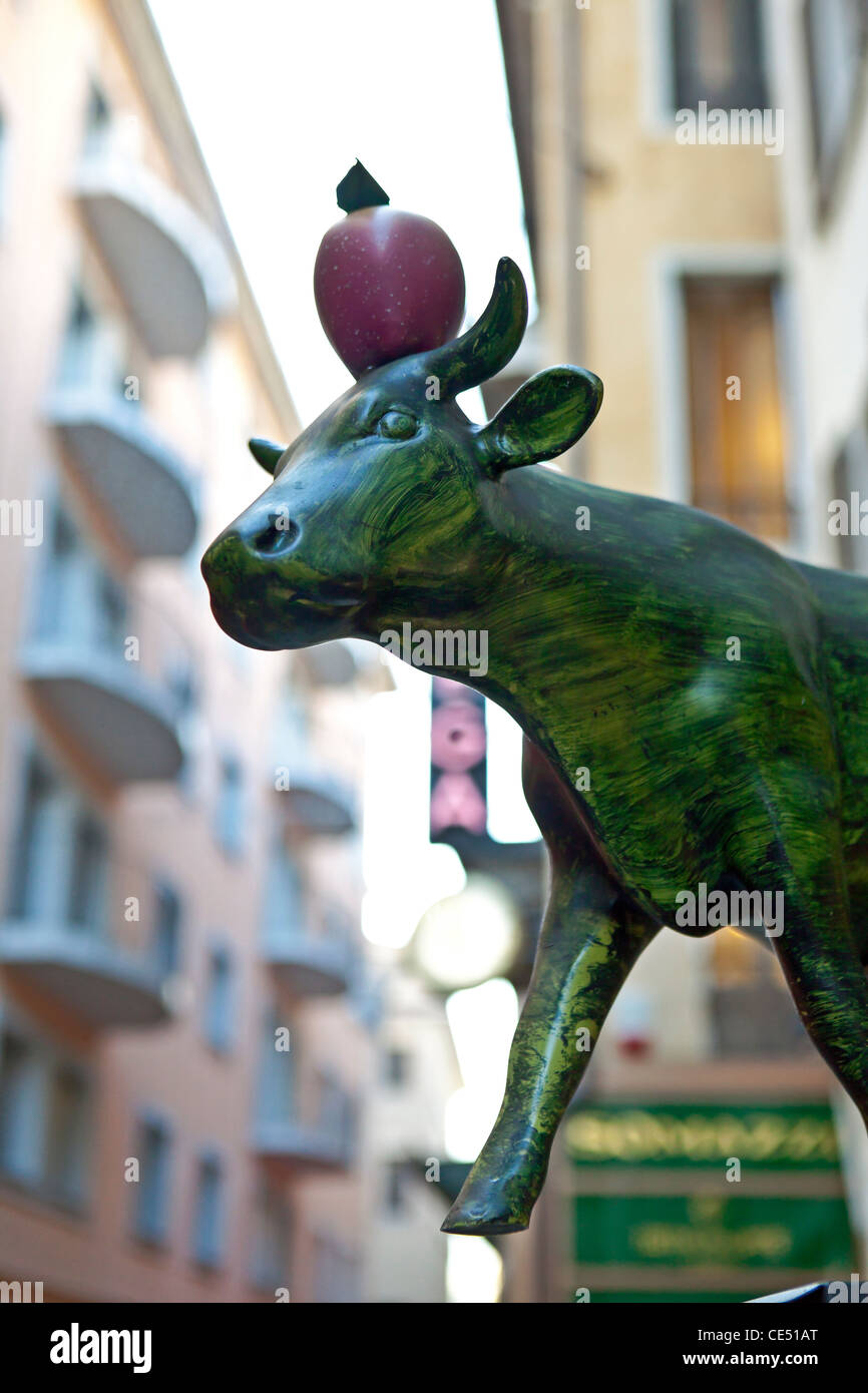 Symbol for Switzerland: Swiss cow with William Tell, apple on the head. Seen in Lugano, Ticino, Switzerland. - Stock Image