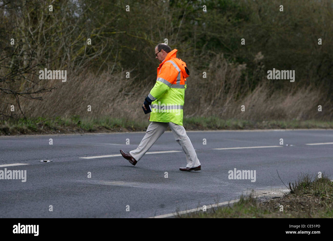 An investigator measures an area of road were a fatal Road Traffic Accident occurred. Picture by James Boardman. Stock Photo
