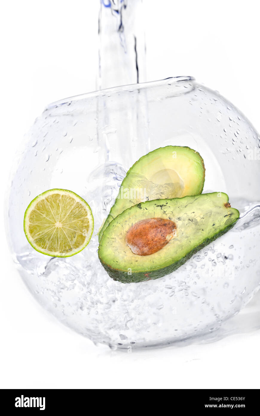 Green limes and avocado in water dropped isolated on a white - Stock Image