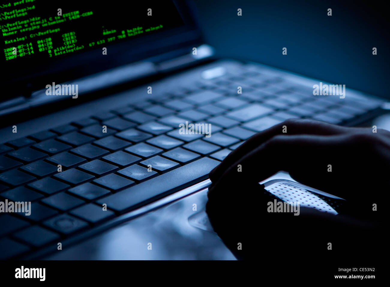 Hacker using laptop. Lots of digits on the computer screen. - Stock Image