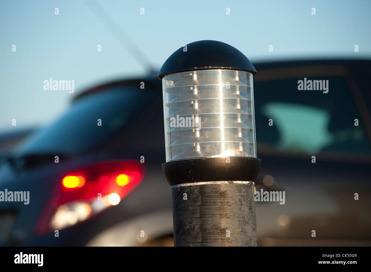 Close up of a lamp in a car park at dusk. - Stock Image