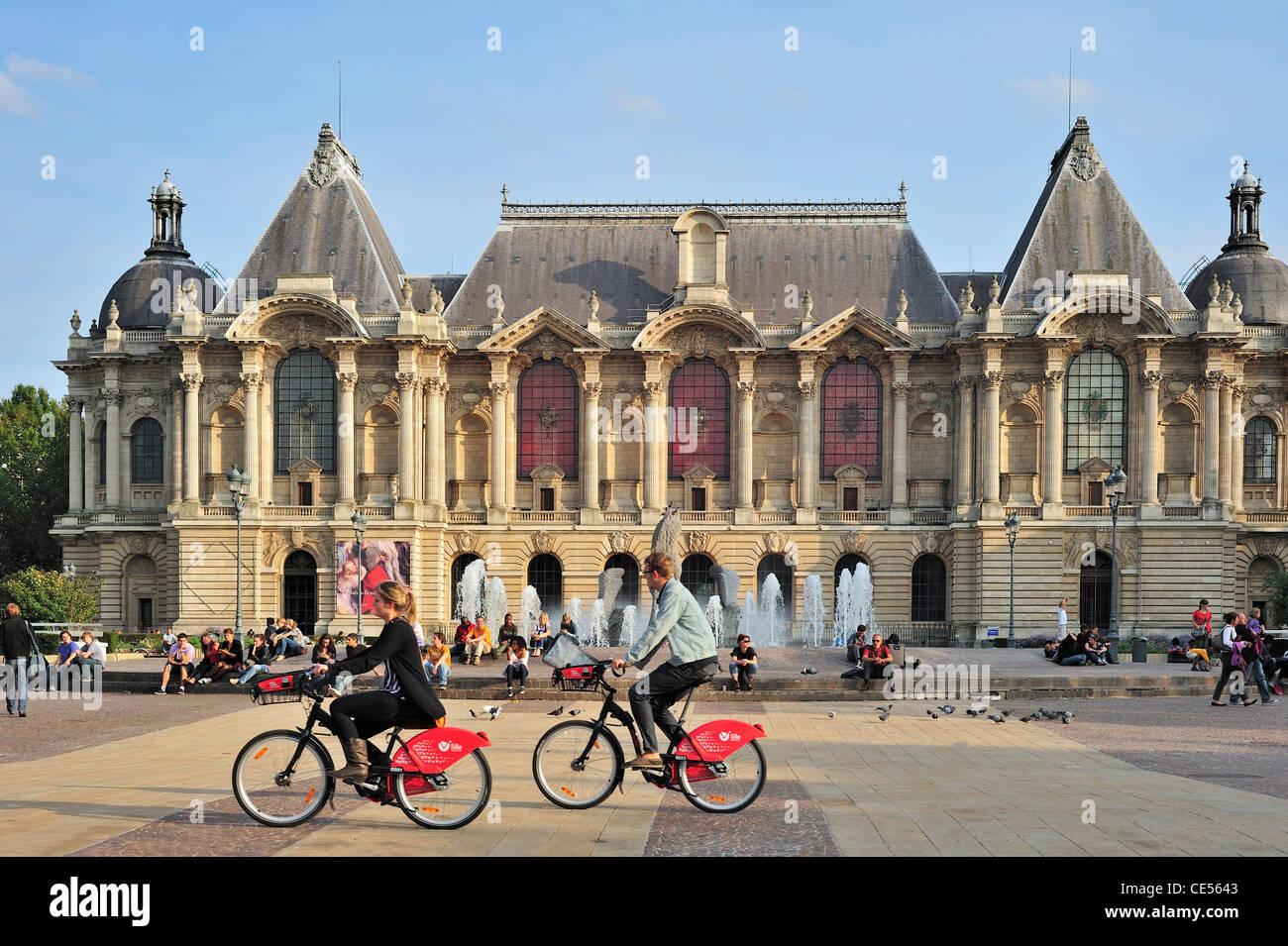 The Palais des Beaux-Arts de Lille / Lille Palace of Fine Arts and tourists riding rental bikes of V'Lille, France Stock Photo