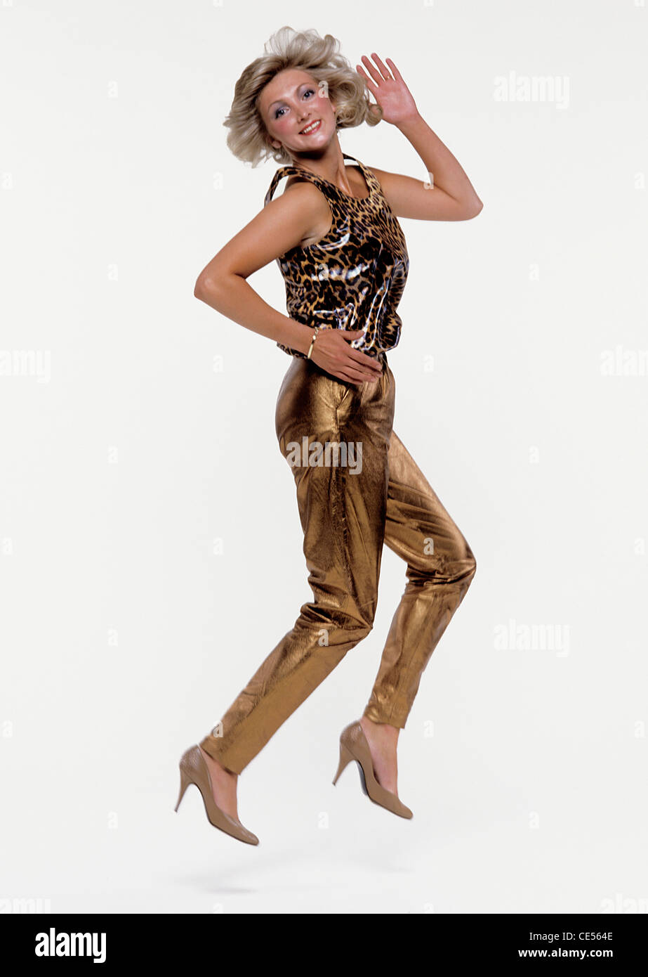 Disco Girl dancing in gold lamé outfit - Stock Image