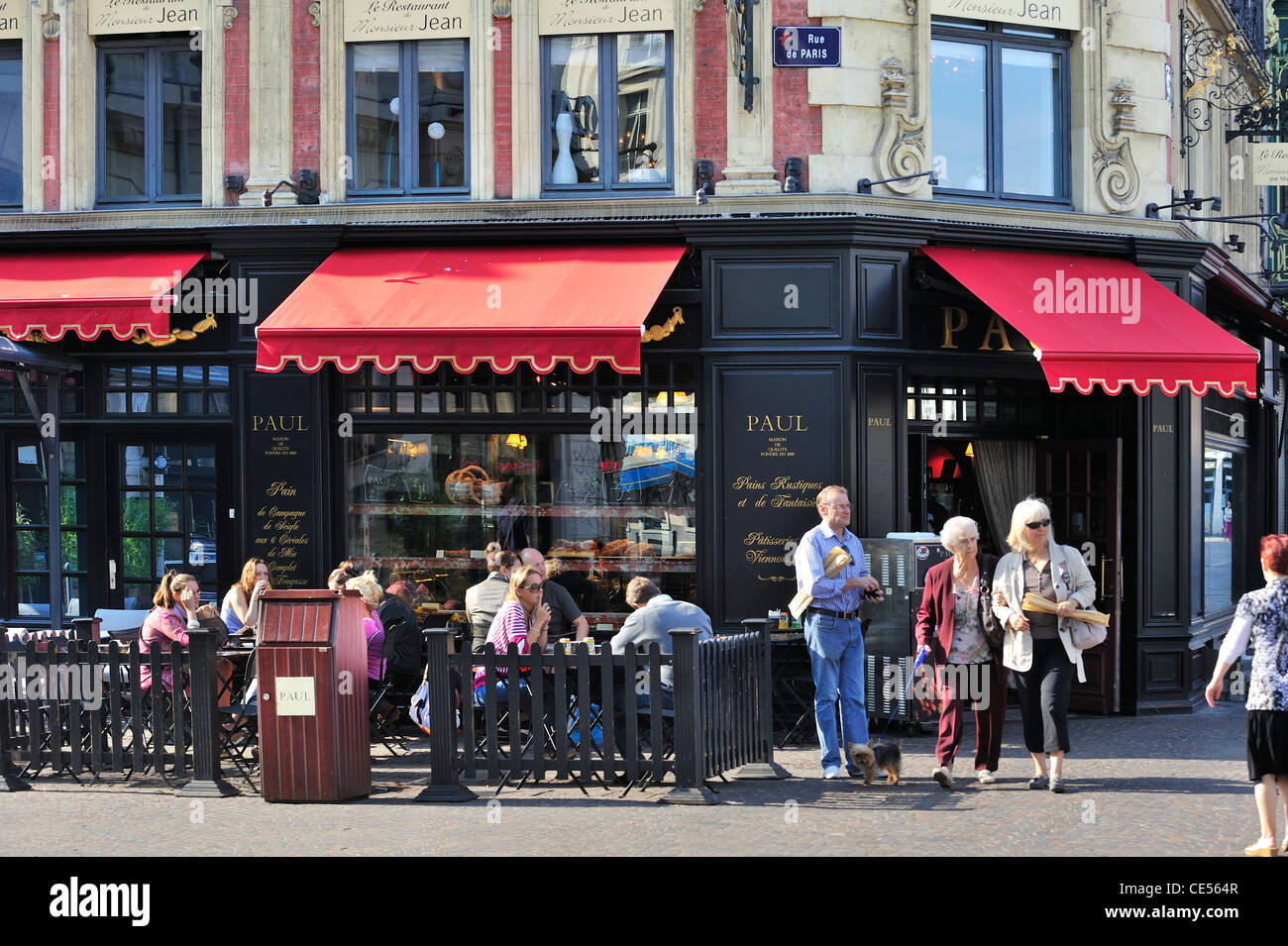 Tourists eating pastries on terrace at the famous bakery and pastry shop Patisserie Paul in Lille, France - Stock Image