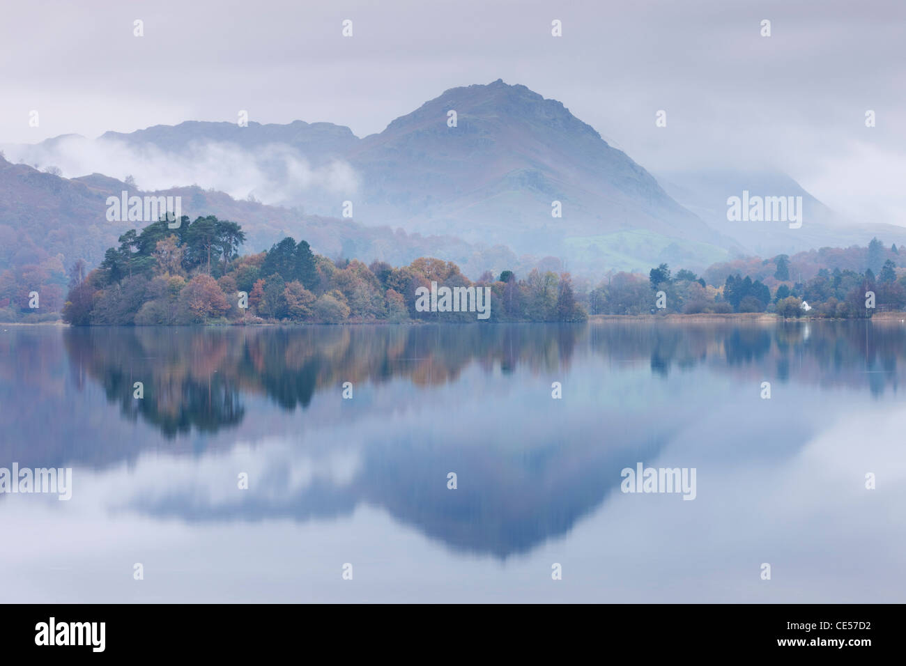 Mist hangs over the lake and island at Grasmere with Helm Crag beyond, Lake District, Cumbria, England. Autumn (November) - Stock Image