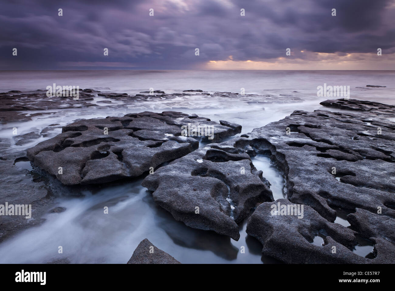 Waves rush around eroded rock ledges at Southerndown on the Glamorgan Heritage Coast, Wales, UK. Winter (December) - Stock Image
