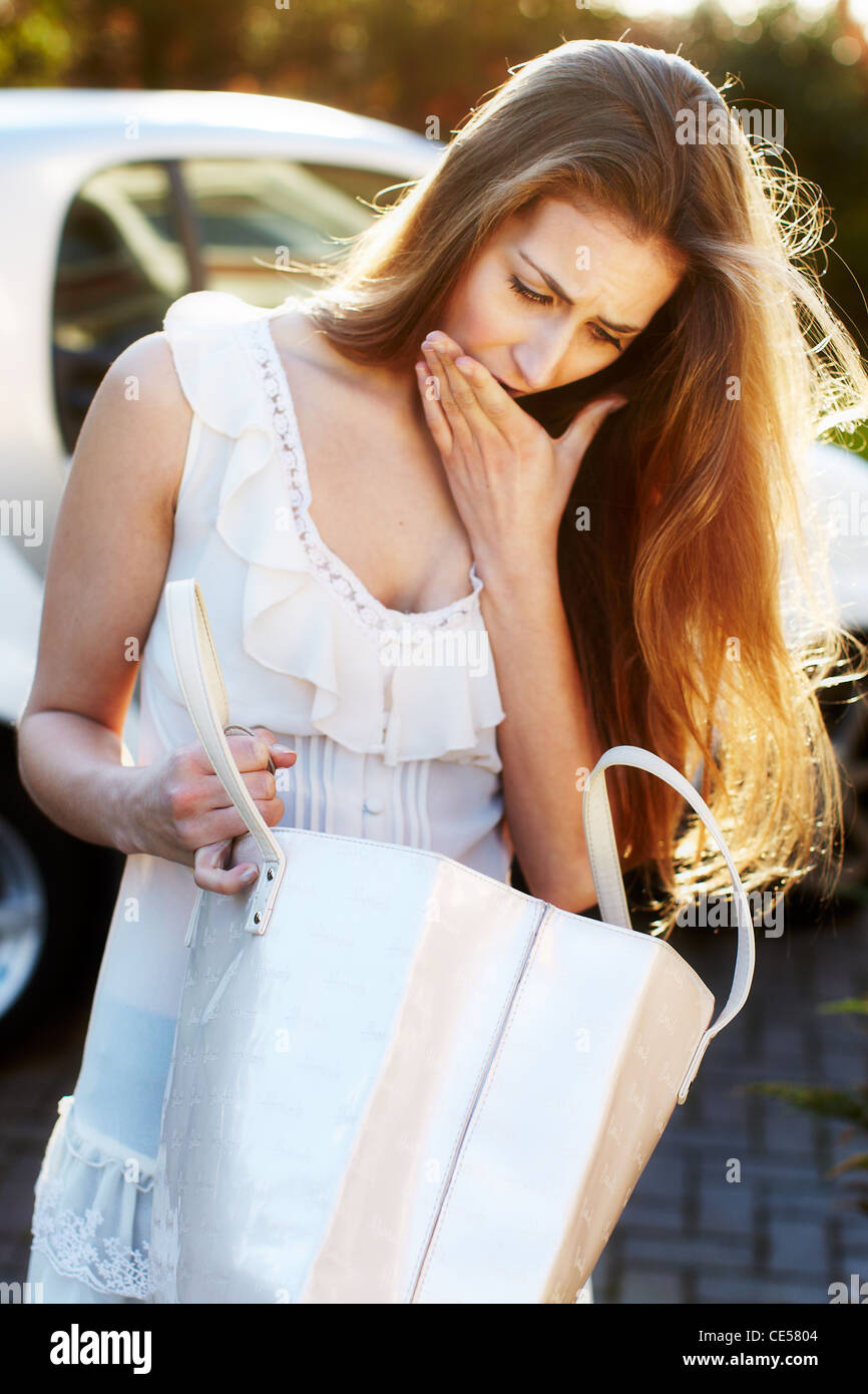 Woman looking for her lost keys - Stock Image