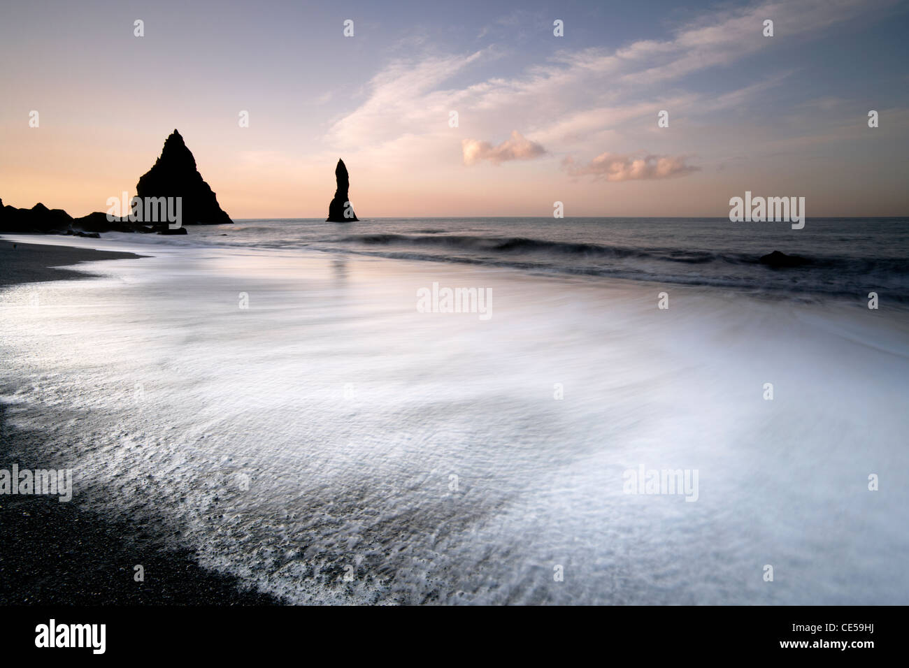 Waves washing in around black volcanic sea stacks on the Vik coast in Iceland Stock Photo