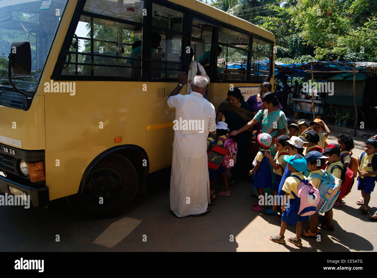 Lot of Small Nursery School children entering in school Bus and Teachers helping them to climb the steps in school - Stock Image