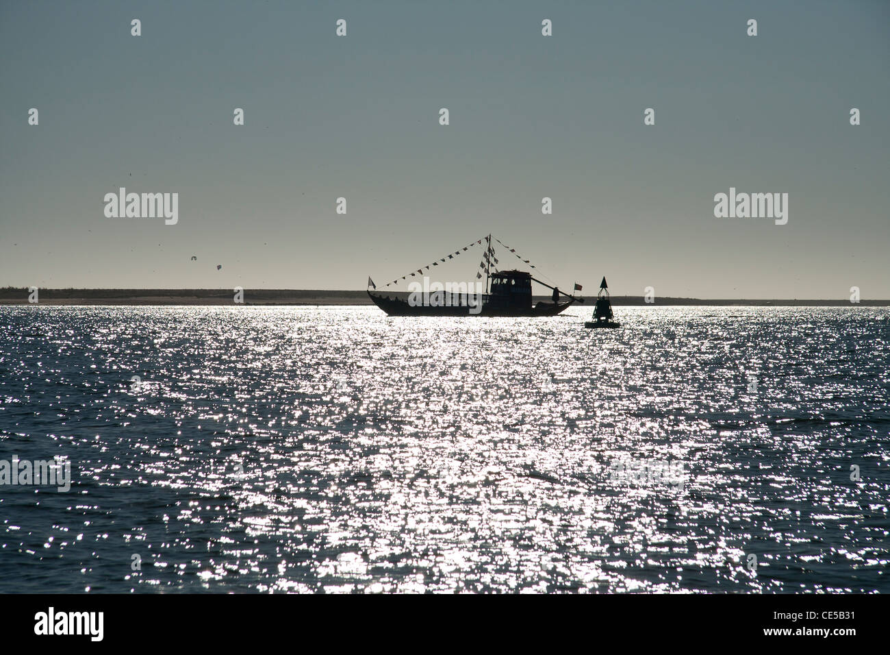 Barco Rabelo silhouette on the Douro river with sun reflection - Stock Image
