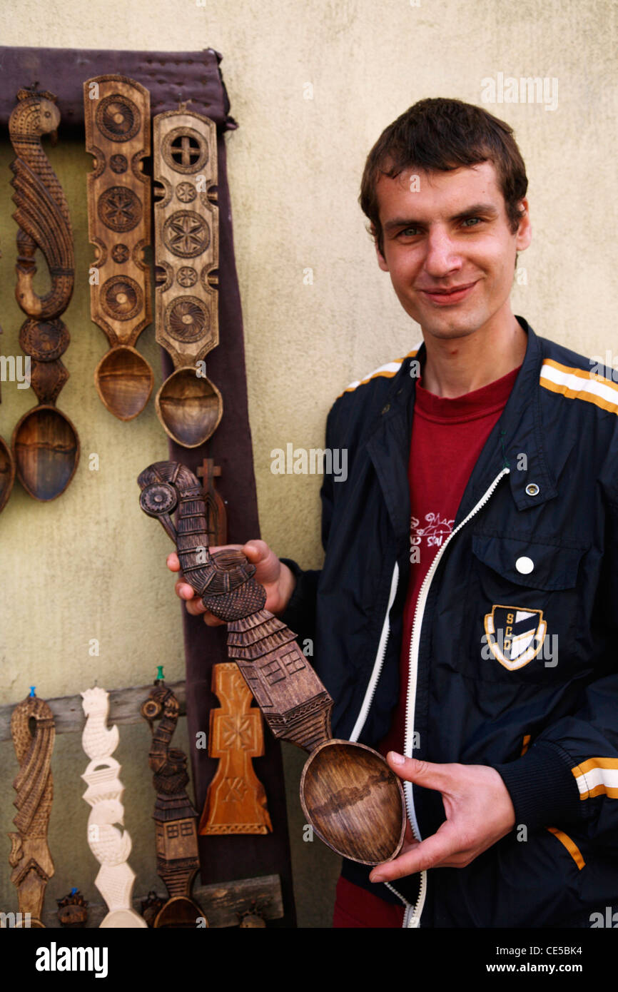 Europe, Romania, Sighisoara, A young man selling wood carved spoons in town center - Stock Image