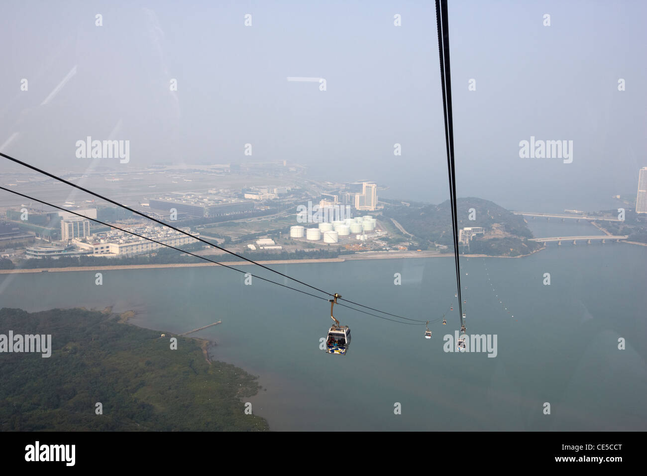 looking through the window of cabin of ngong ping 360 cable car over tung chung bay and international airport lantau - Stock Image
