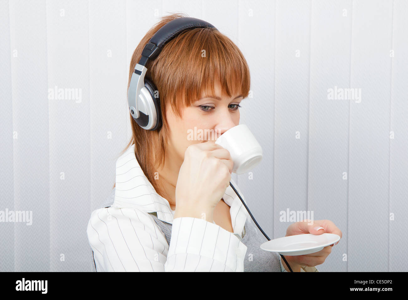 The girl in headphones with a microphone drinks coffee Stock Photo