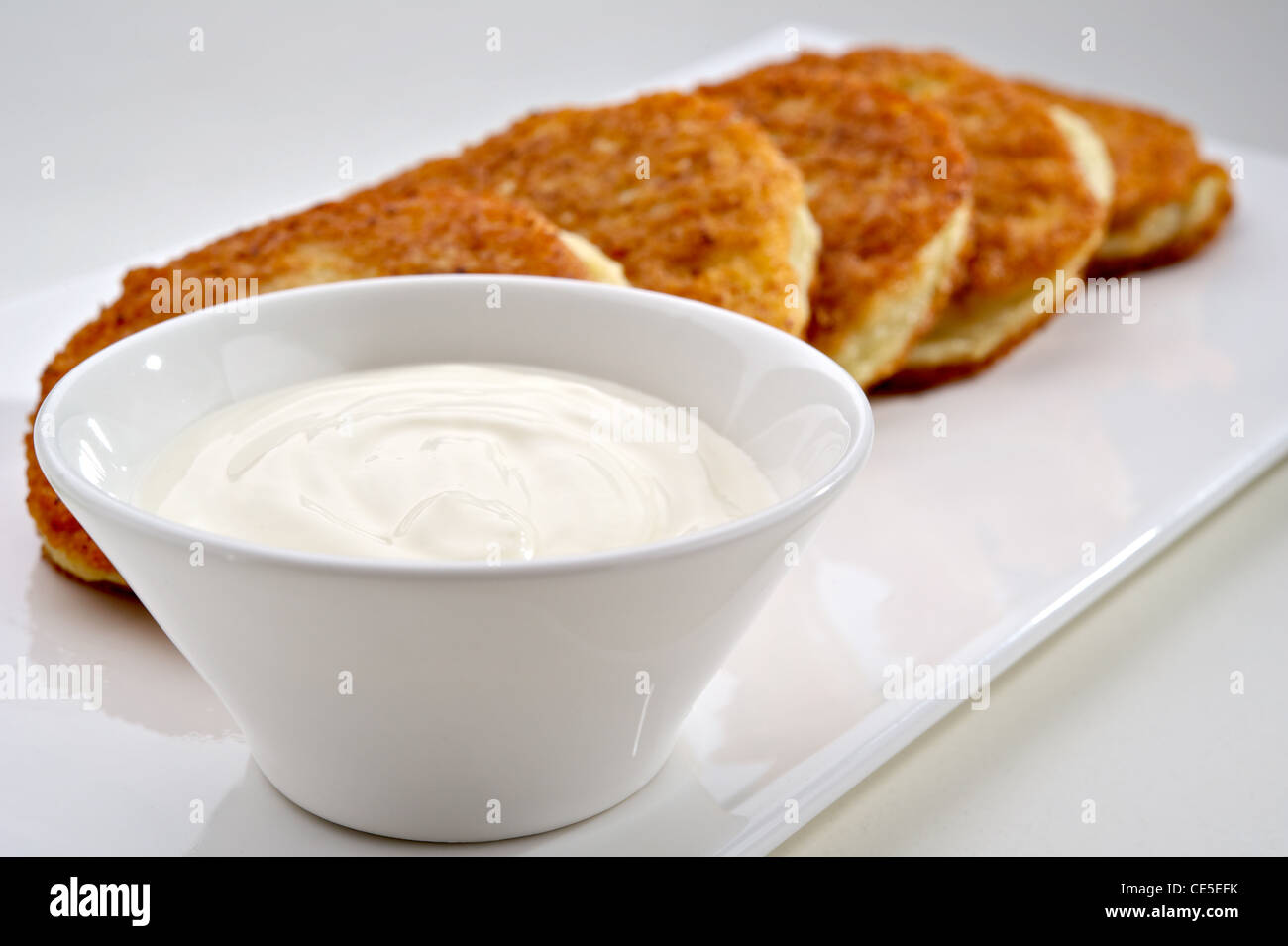 Potato pancakes served on white plate with sour cream - Stock Image