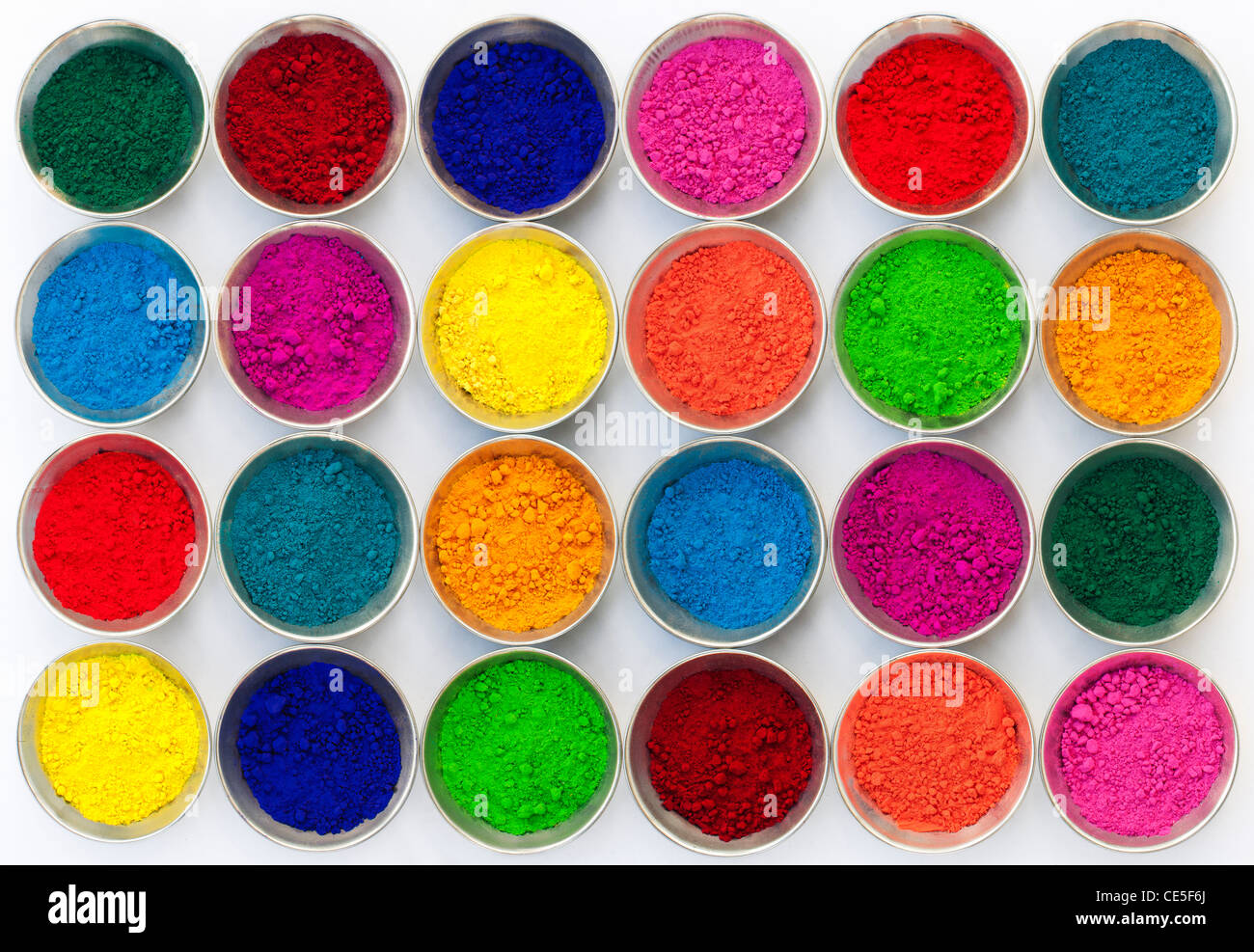 Coloured Indian powder in metal bowls used for making rangoli designs. White Background Stock Photo