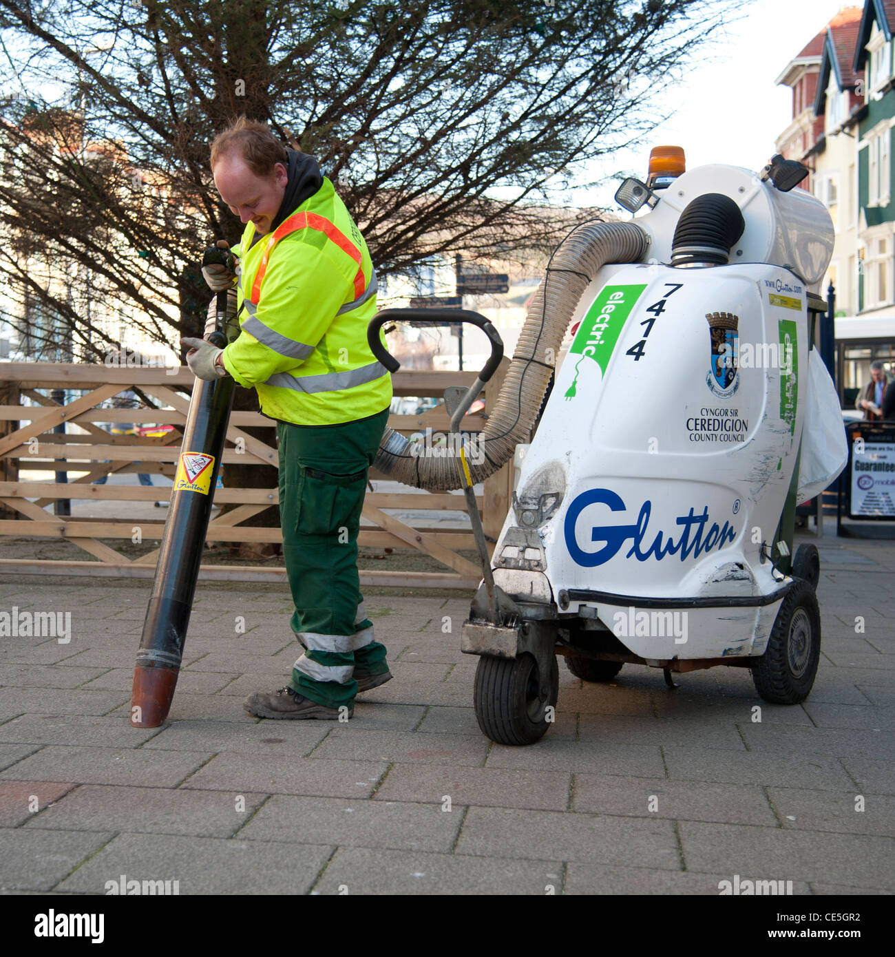 A local authority council worker using a Glutton electric industrial vacuum cleaner to pick up street litter, UK - Stock Image