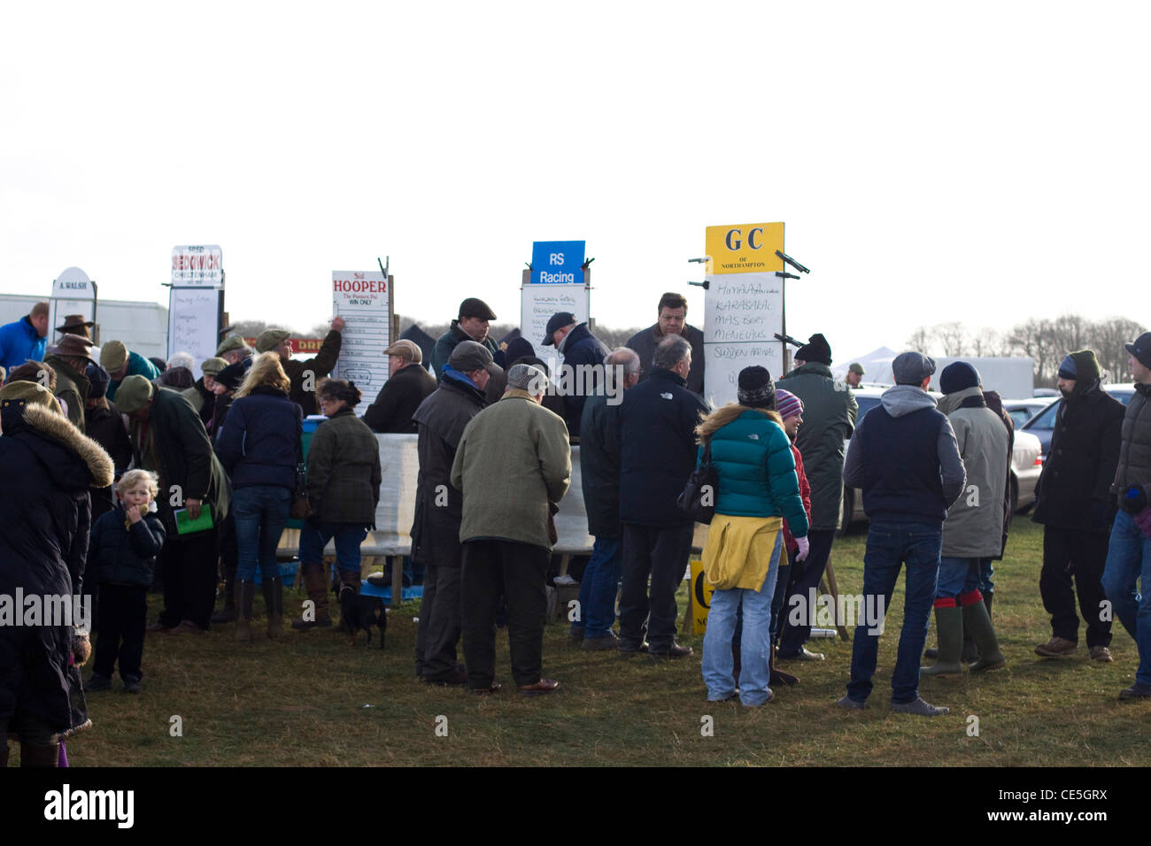 Crowds gathering to place bets with the line of Bookies on stands for the next Horse Race - Stock Image