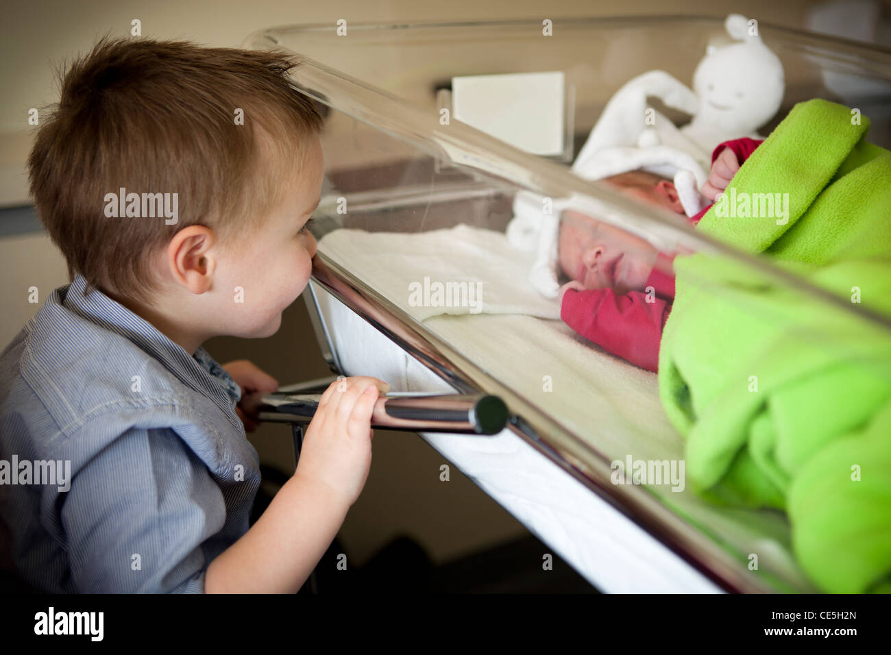 A child boy is looking at his newborn sister at maternity. - Stock Image