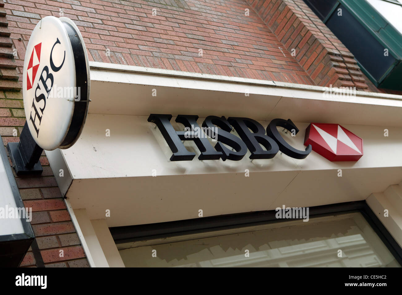 Circular HSBC Sign,  Royal Avenue, Red , White corporate logo, HSBC Lettering. Cream frontage, red brick wall - Stock Image
