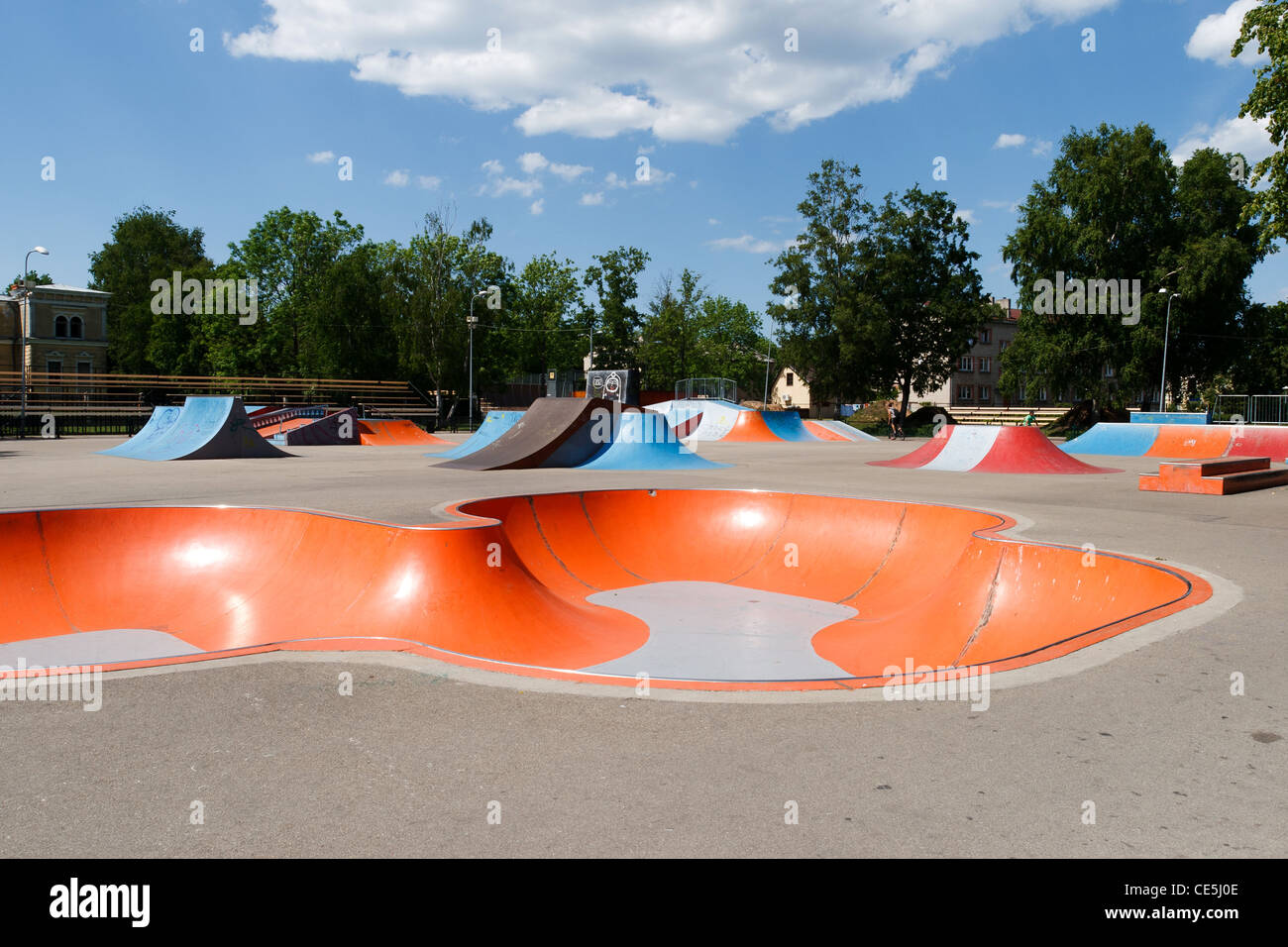Empty skatepark with colorful ramps in sunny day - Stock Image