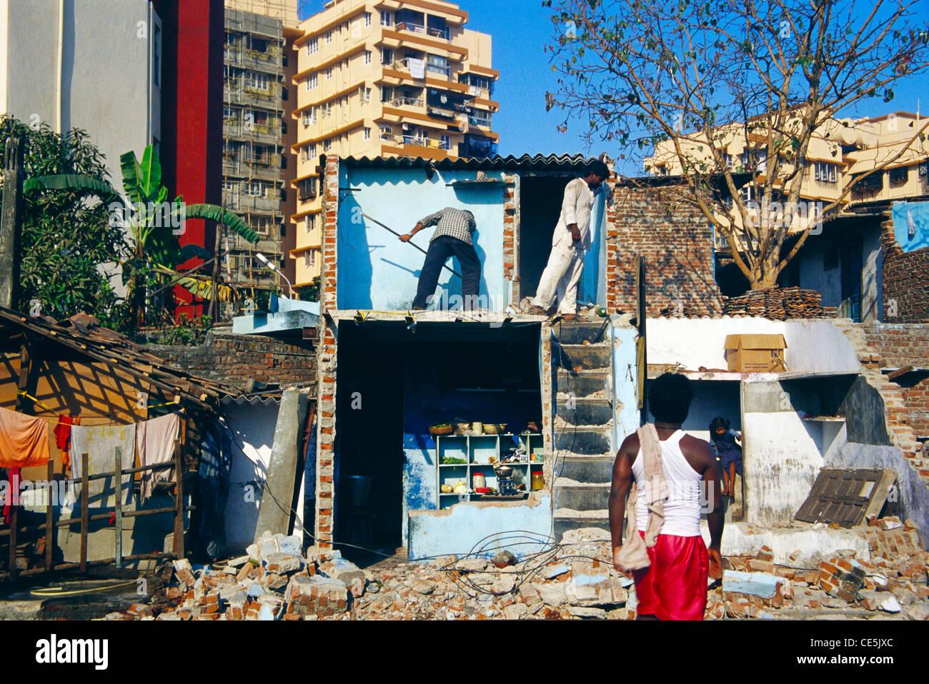 Slum house illegal demolished broken below modern buildings bombay mumbai maharashtra India - Stock Image