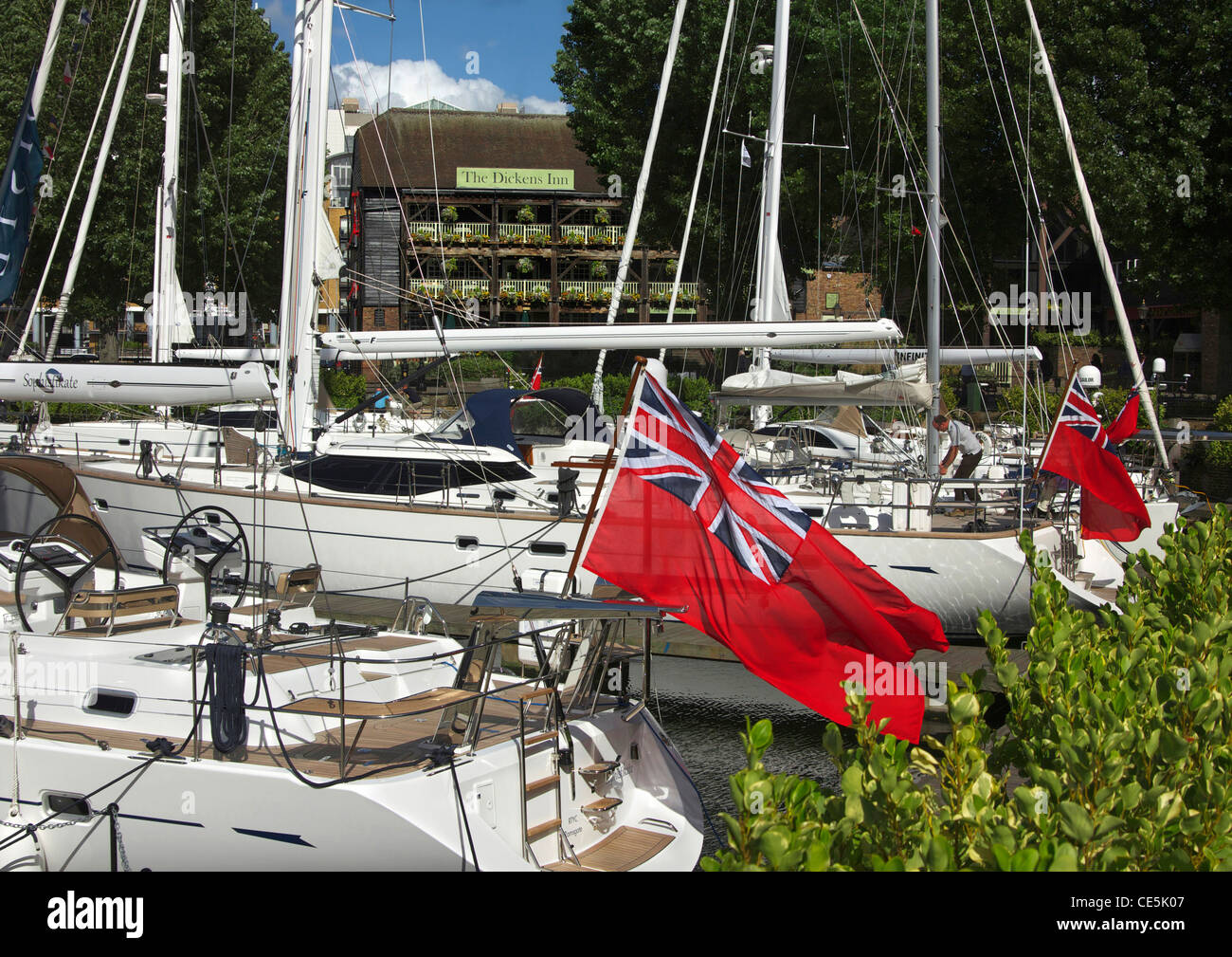 Red Ensign flags flying on yachts moored next to The Dickens Inn in St. Katharine's Dock, London, England, UK. - Stock Image