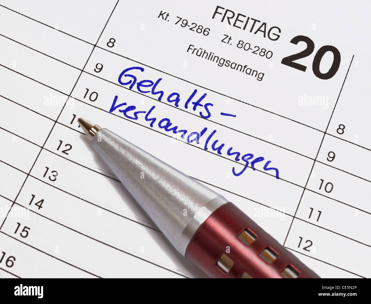 A calendar shows March the 20th, the item salary negotiations is in the calendar written with German words. Beside - Stock Image