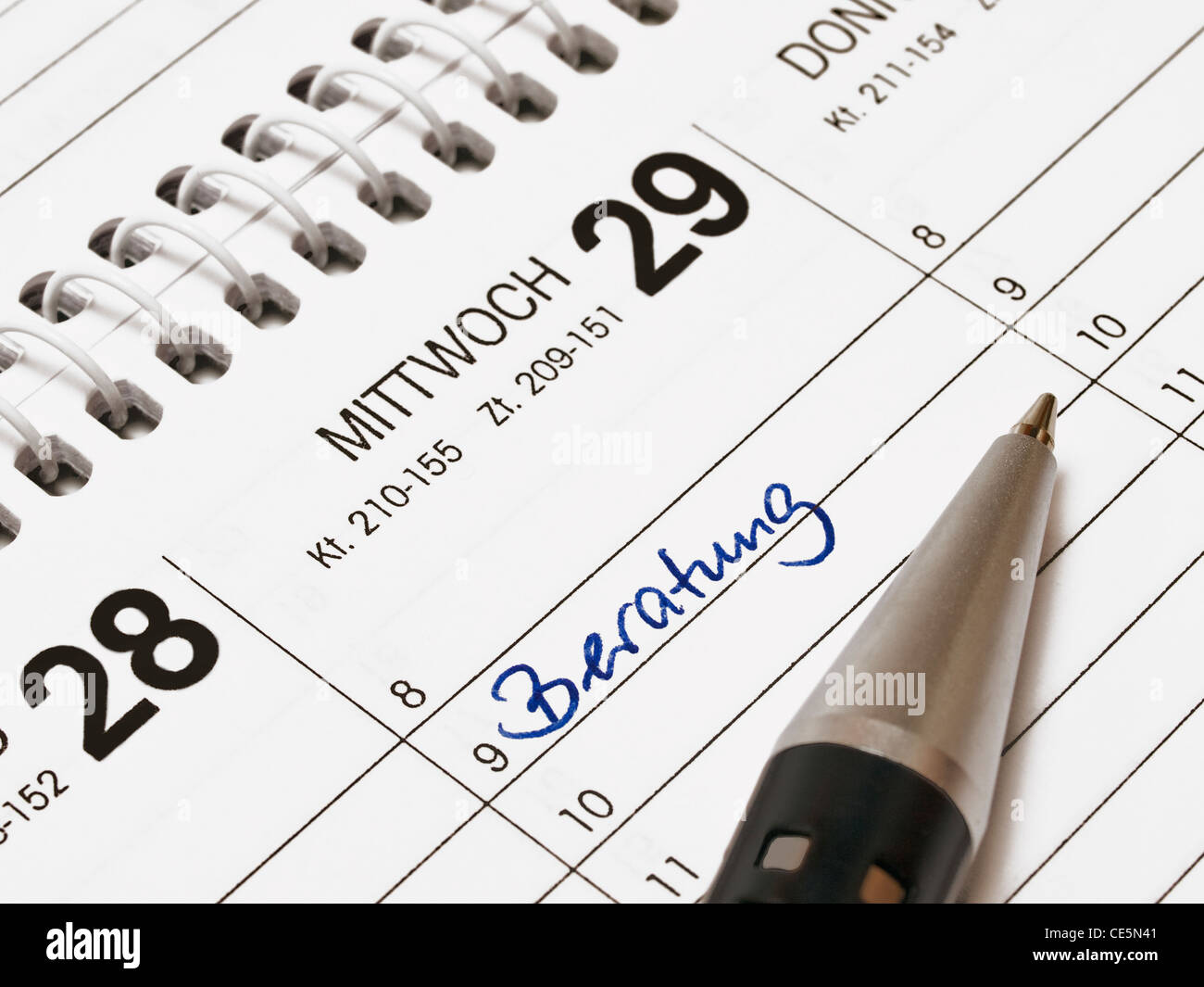 A calendar shows Wednesday, the 29th of a month. The item meeting is in the calendar written with German words. - Stock Image