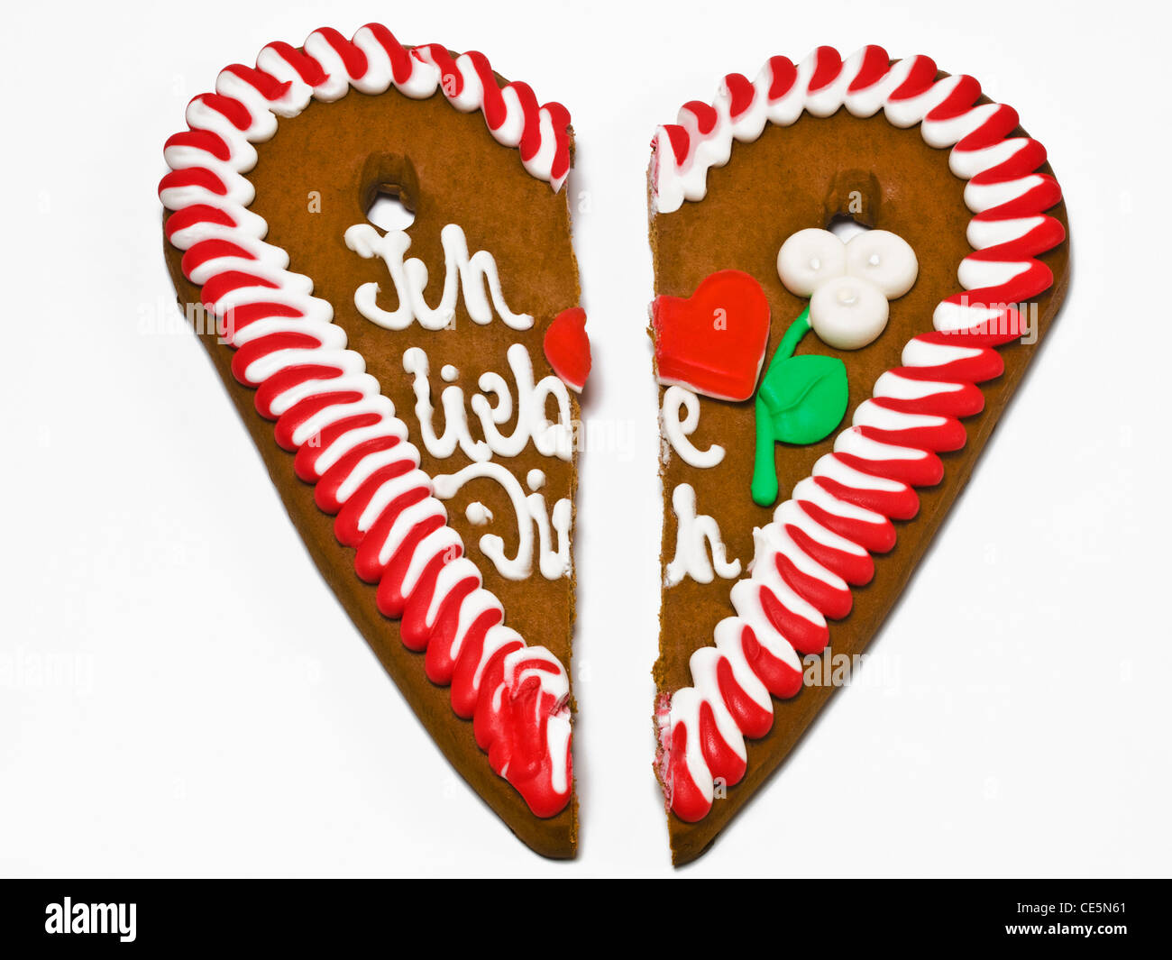 a broken gingerbread heart with the inscription I love you in German - Stock Image
