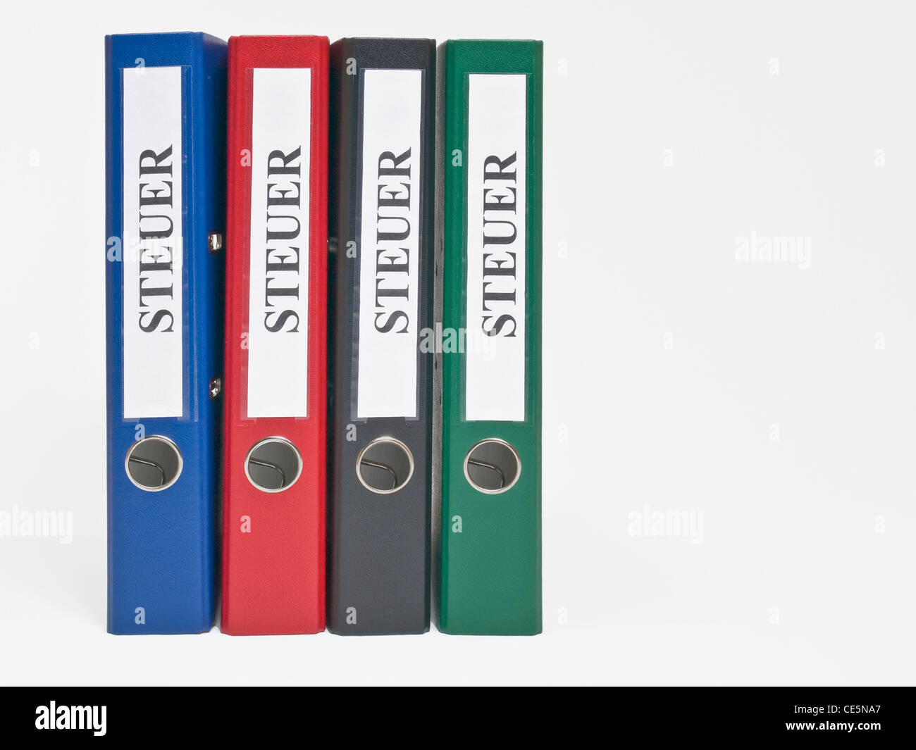 vier bunte, stehende Ordner beschriftet mit 'Steuer' | four colored files upright with the German label - Stock Image