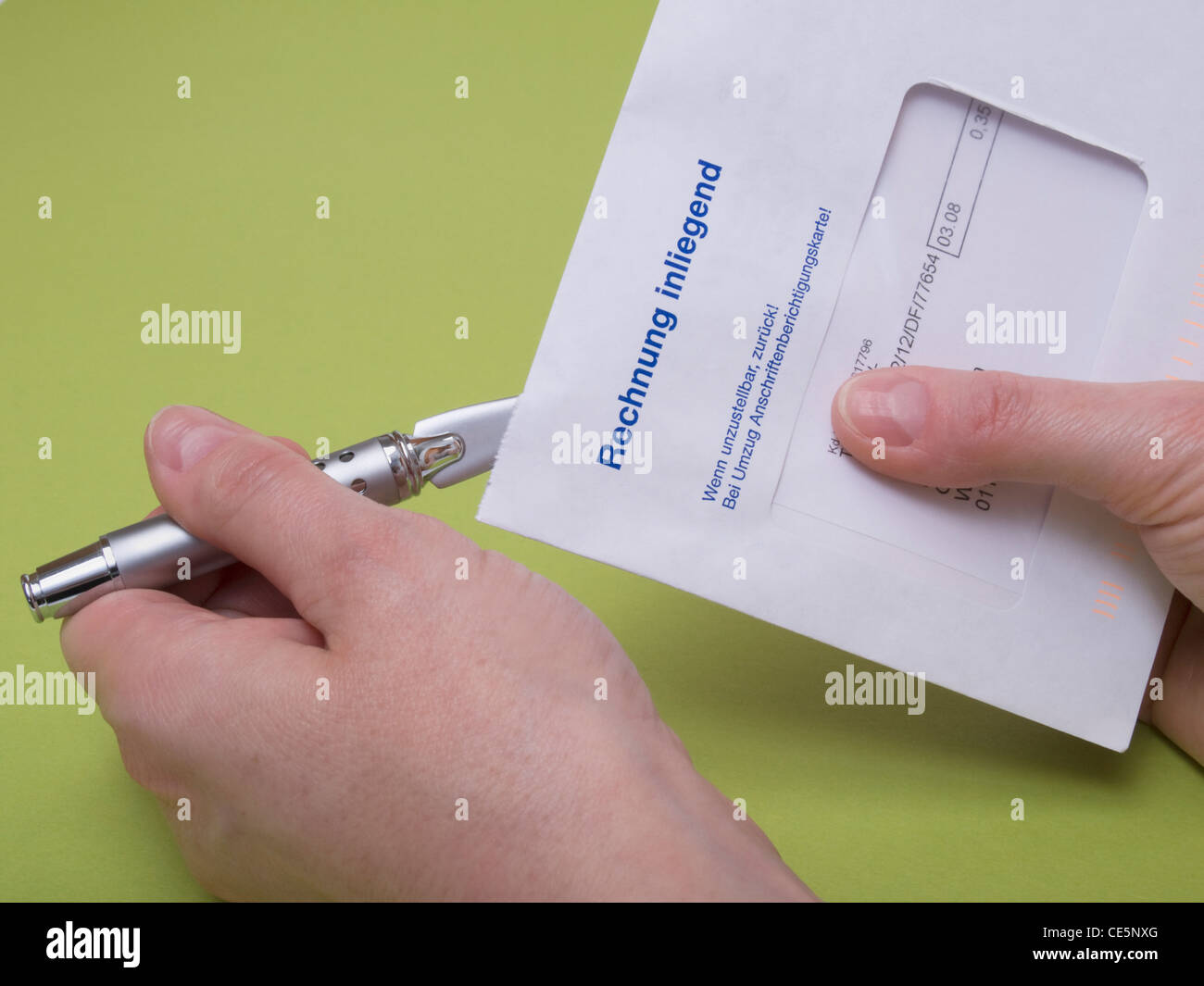 a letter with the remark ' invoice enclosed ' in German is opened with a letter opener - Stock Image