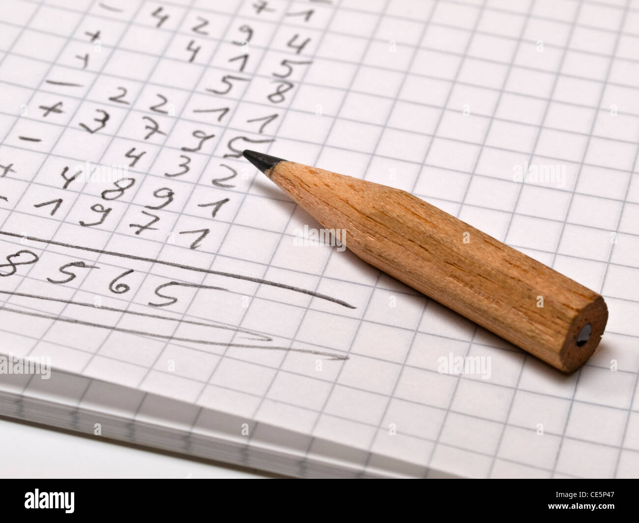 a checked memo pad with a long sequence of numbers, beside is a small pencil - Stock Image