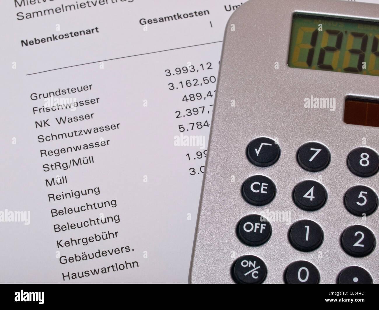 ein Taschenrechner liegt auf einer Nebenkostenabrechnung | a calculator of a accounting of service charges - Stock Image