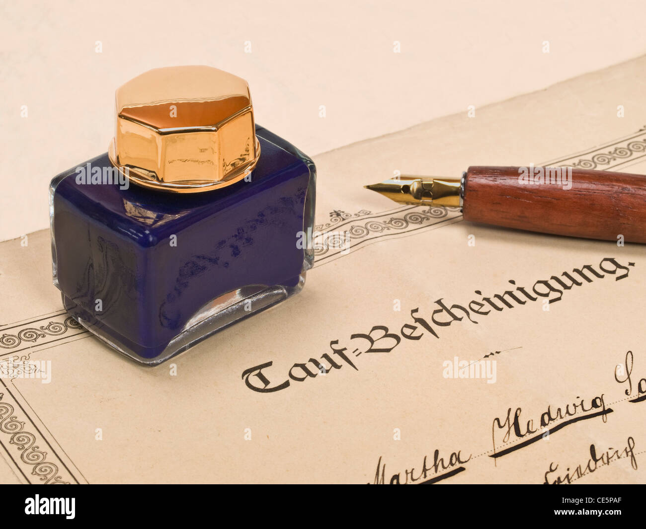 Detail photo of a christening attestation from the year 1890, on it is a ink pot and a pen - Stock Image