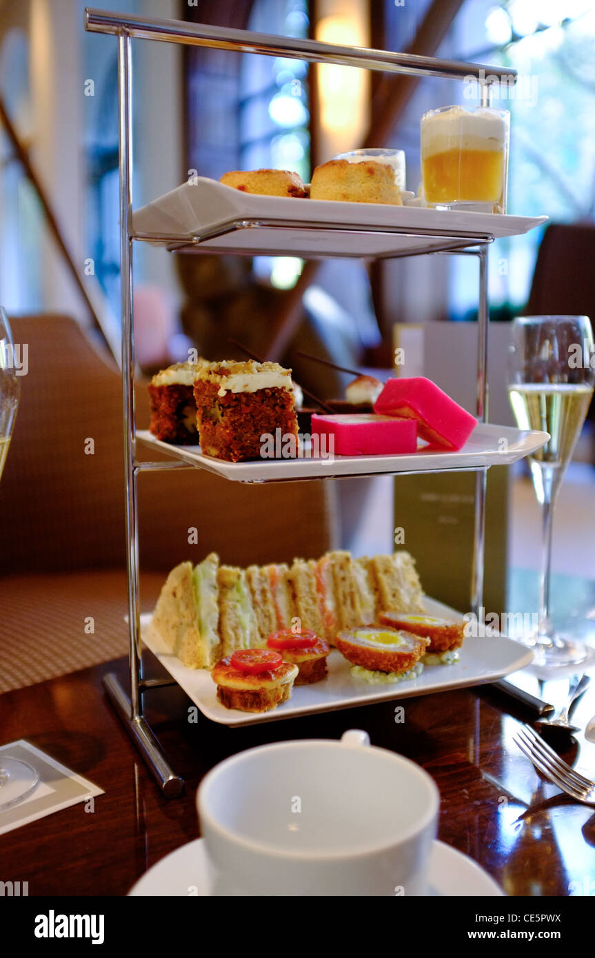 Three tier cake plate, arranged with cream tea sandwiches and cakes.  Champagne glass in background and tea cup - Stock Image