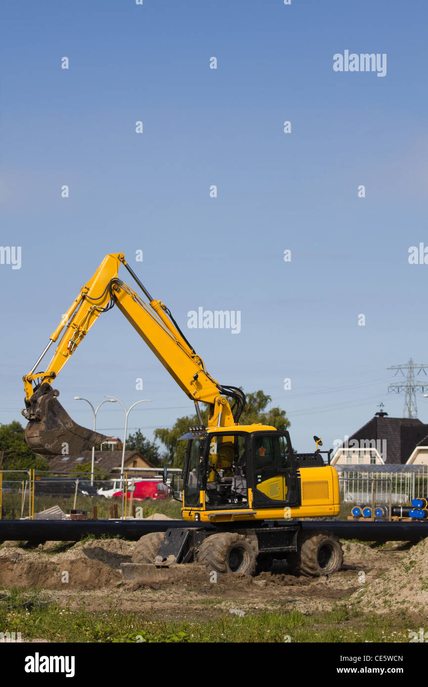 Excavator at work digging up ground for new to build houses - vertical Stock Photo